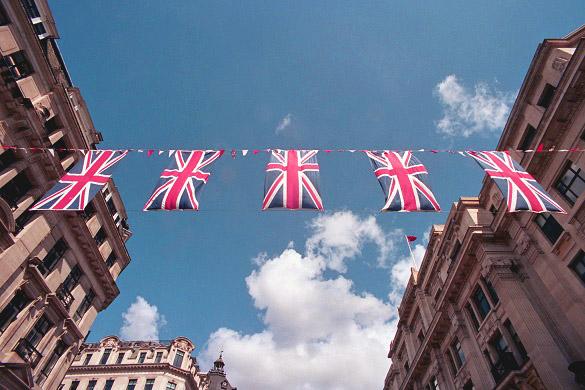 Imagen de la bandera del Reino Unido ondeando entre edificios