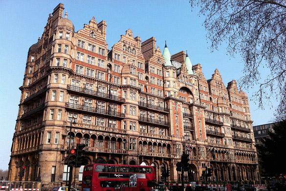 : Imagen de la fachada del antiguo Hotel Russell delante de un autobús de dos pisos