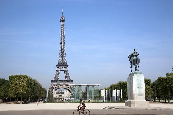 Imagen de una persona en bici frene a la Torre Eiffel en París.
