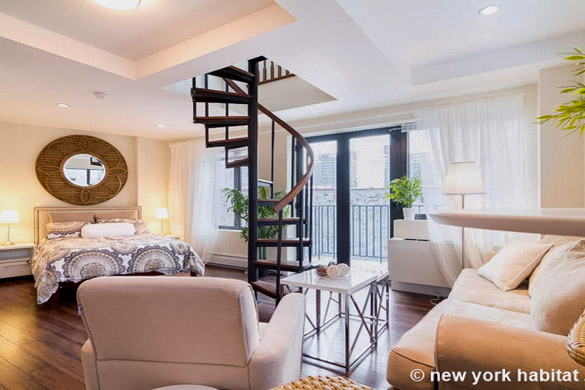 Imagen de la zona de descanso y de las escaleras de caracol en el apartamento NY-16334, con un espejo circular en el fondo.
