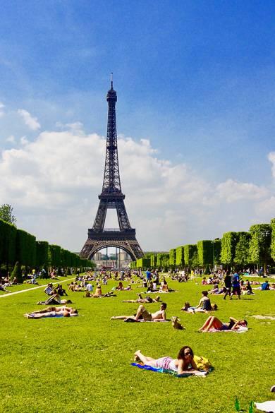 Personas tumbadas en el césped del Campo de Marte con la Torre Eiffel de fondo