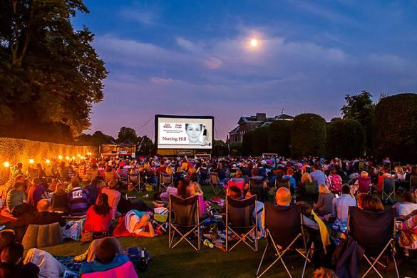 Personas sentadas al aire libre viendo una gran pantalla de cine