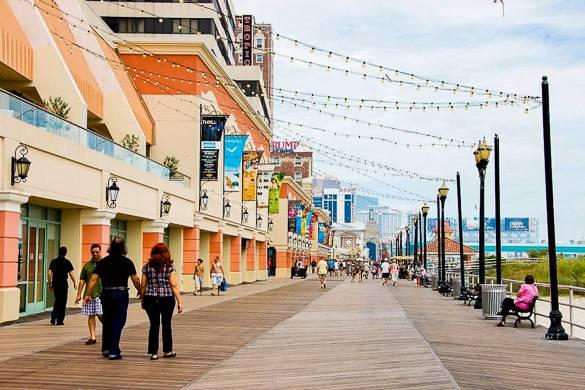 Imagen de gente caminando por el paseo marítimo entarimado de Atlantic City, flanqueado por casinos y hoteles