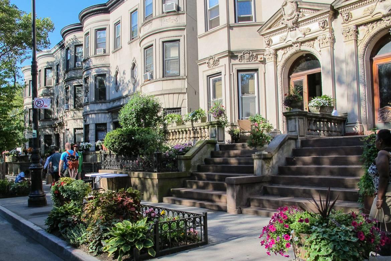 Imagen de una calle del barrio de Brooklyn con casas adosadas y jardines.