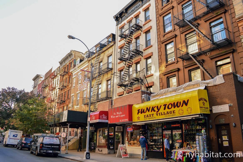 Imagen de una calle de East Village con apartamentos, salidas de incendios y escaparates.
