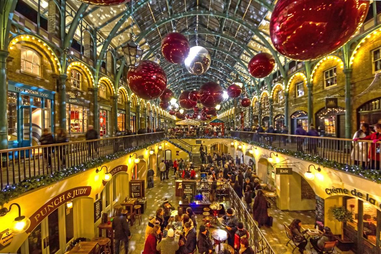 Imagen de las tiendas de Covent Garden con luces y adornos colgados del techo.