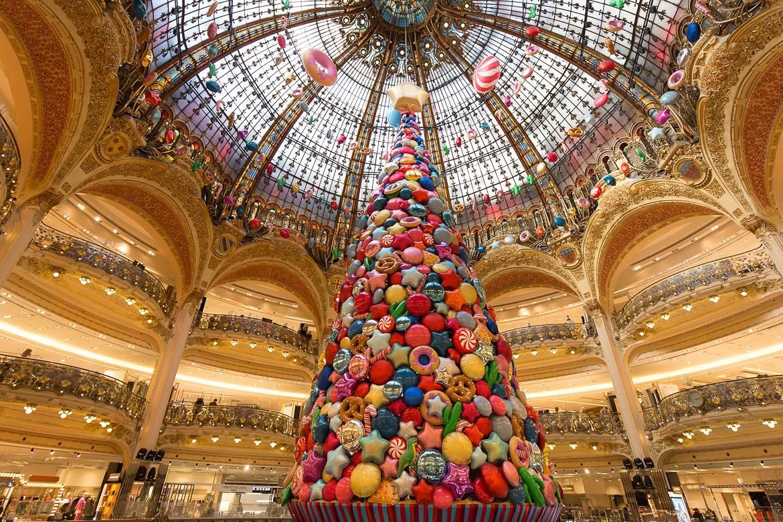 Imagen del interior de las Galerías Lafayette, con balcones abovedados, árbol de Navidad, decoración y techo de cristal.
