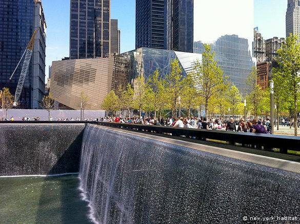 A view of the north World Trade Center pool with the 9/11 Memorial Plaza and Memorial Museum in the background