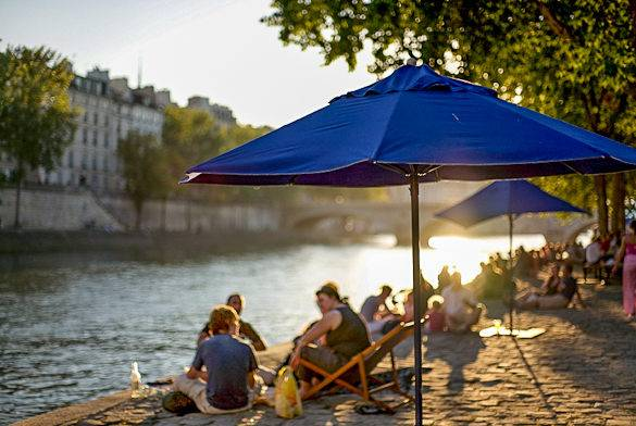 A picture of people sunbathing at the Paris Plage next to the Seine