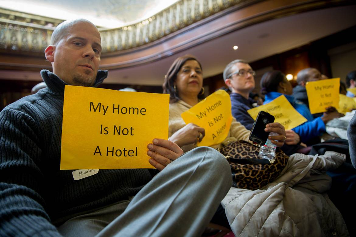 Photo of home owners holding signs to protest against illegal hotels in New York City