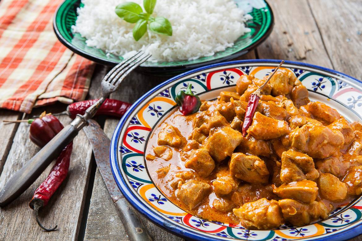 Image of a plate of chicken tikka masala with rice and chili peppers on a wooden table