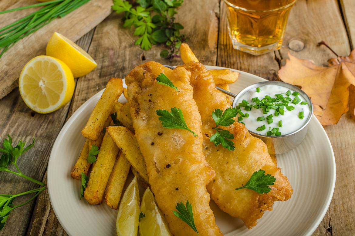Image of fried fish over a plate of French fries with tartar sauce, herbs, lemon, and beer