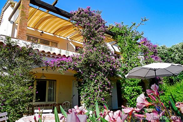 Image of a villa in Provence covered with flowering plants and surrounded by a garden