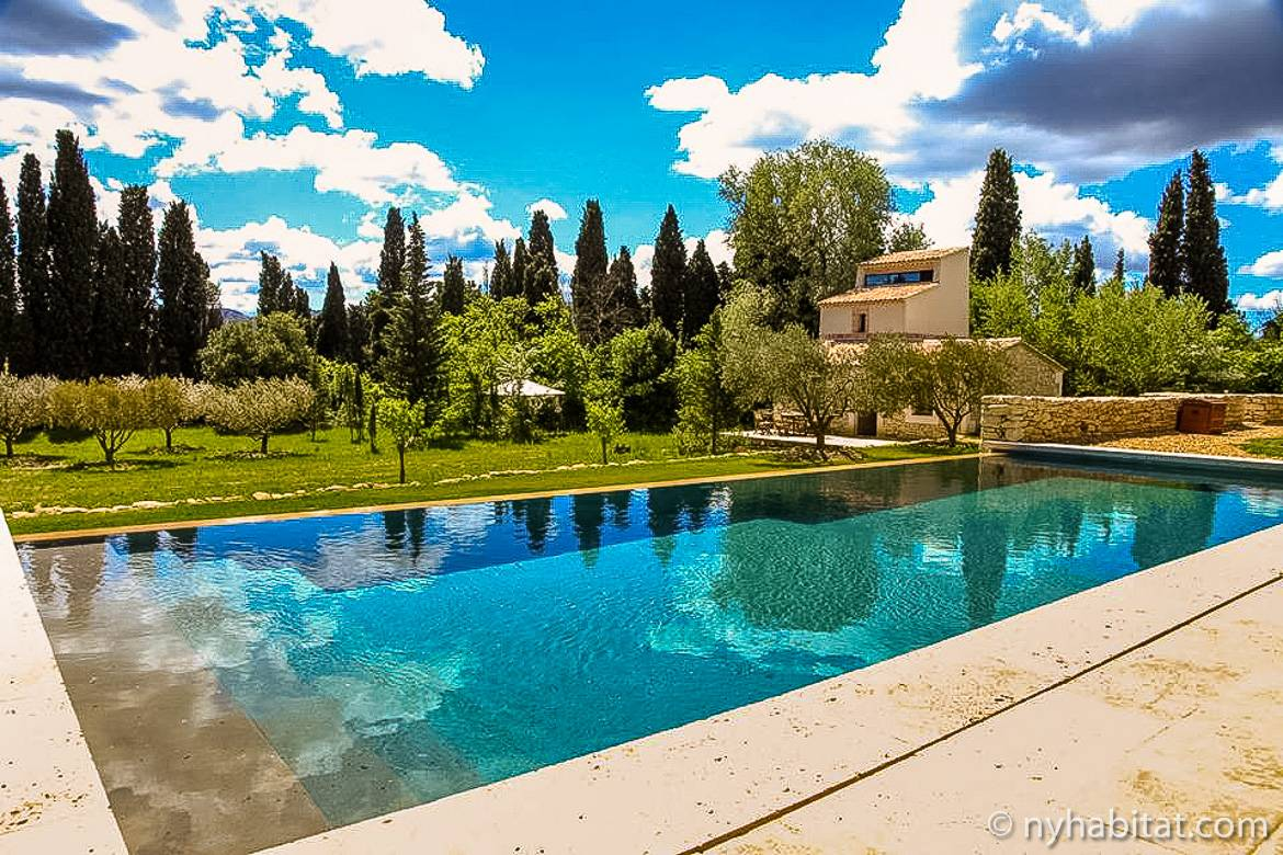 Image of an infinity pool backed by a garden and the guesthouse of a Provençal mas