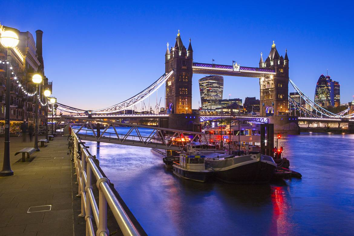 Image of a boat docked on the side of the River Thames near Tower Bridge in London