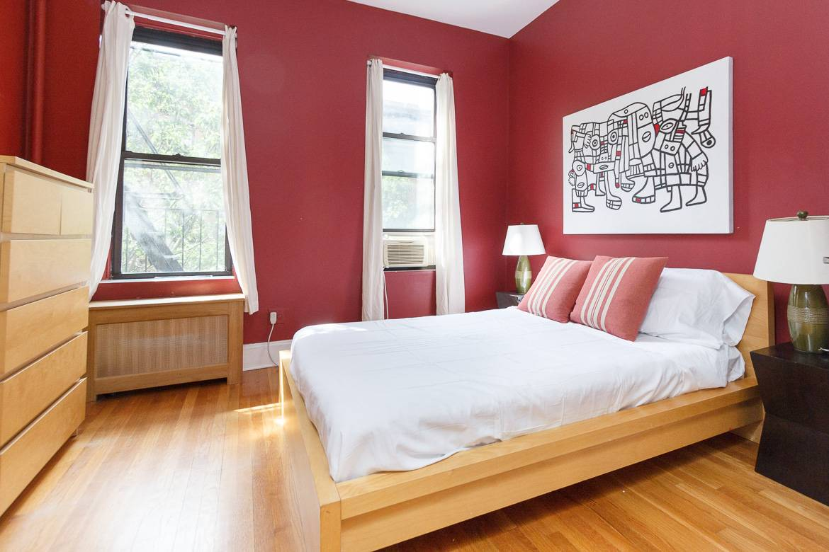 Image of a bedroom in a furnished rental with an air conditioner and fire escape