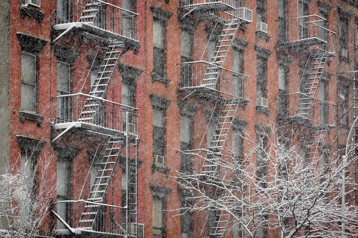Image of a row of low-rise buildings in New York with fire escapes covered in snow