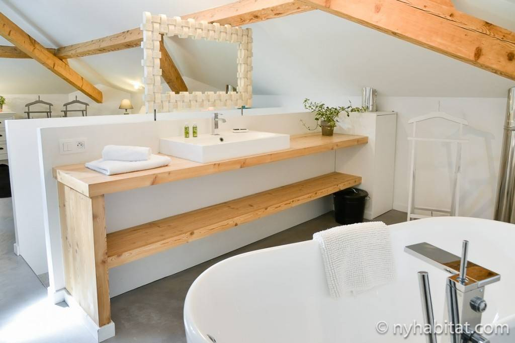 Image of a bathroom with a white bathtub and wooden beams