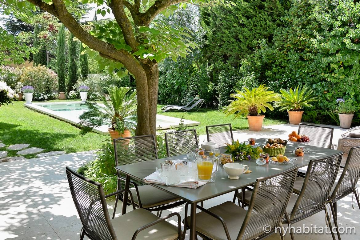 Image of a laden dining table by the pool outside Villa Cézanne