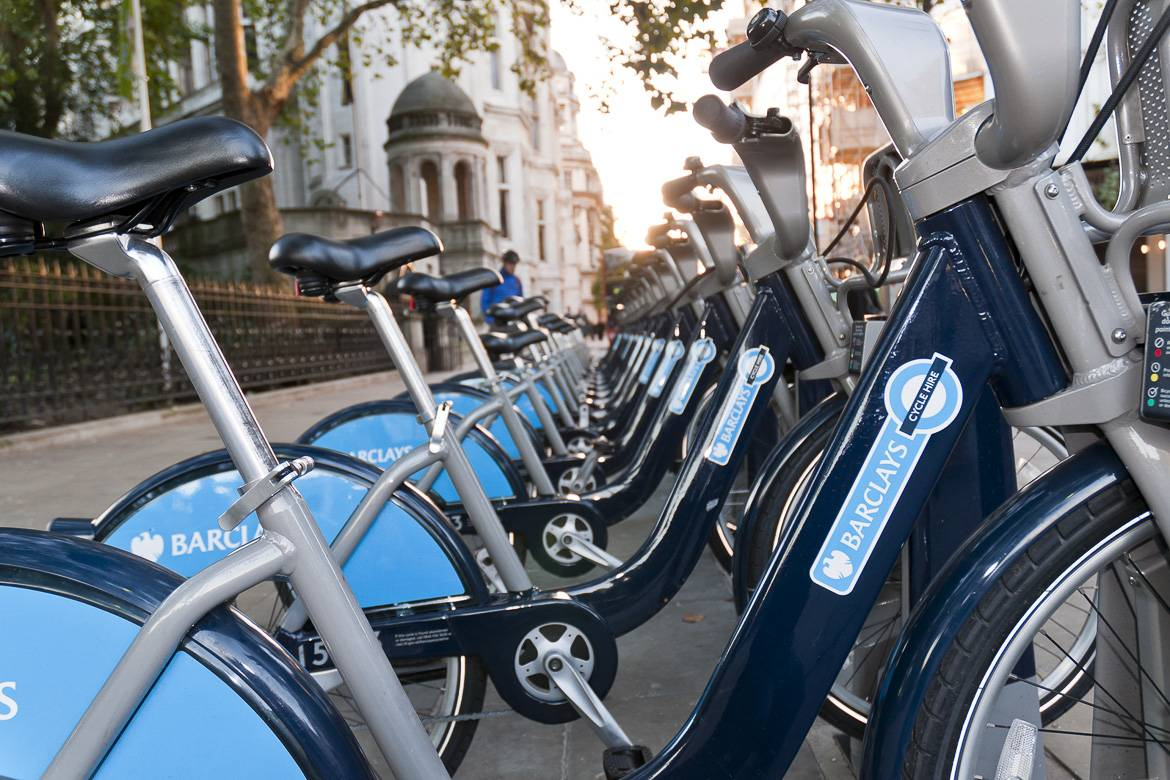 Image of blue Barclay's bicycles on a London sidewalk lined up in a row