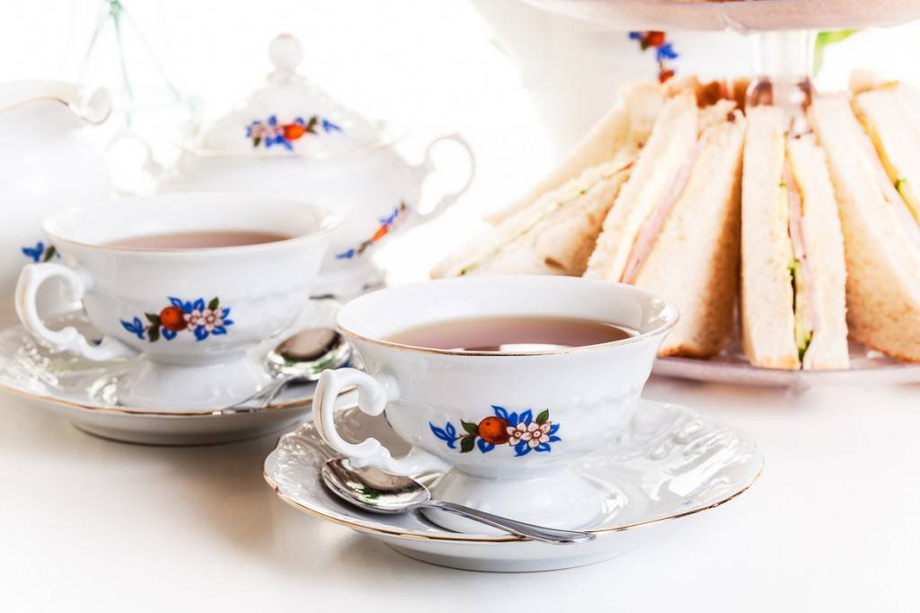 Image of two white teacups and a plate of finger sandwiches