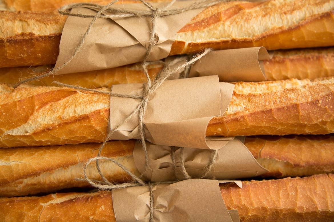 Image of French baguettes stacked and wrapped in paper
