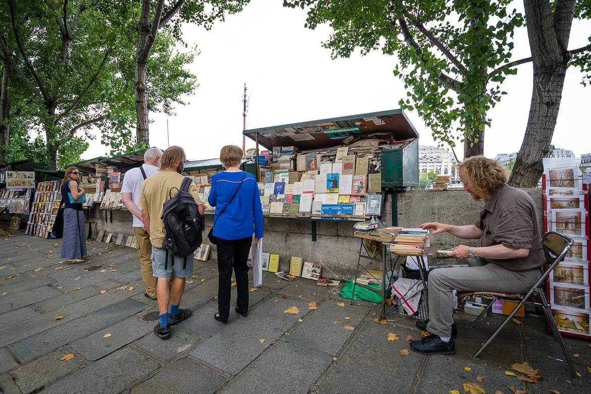 Image of a book seller, or bouquiniste, by his stall next to the Seine River