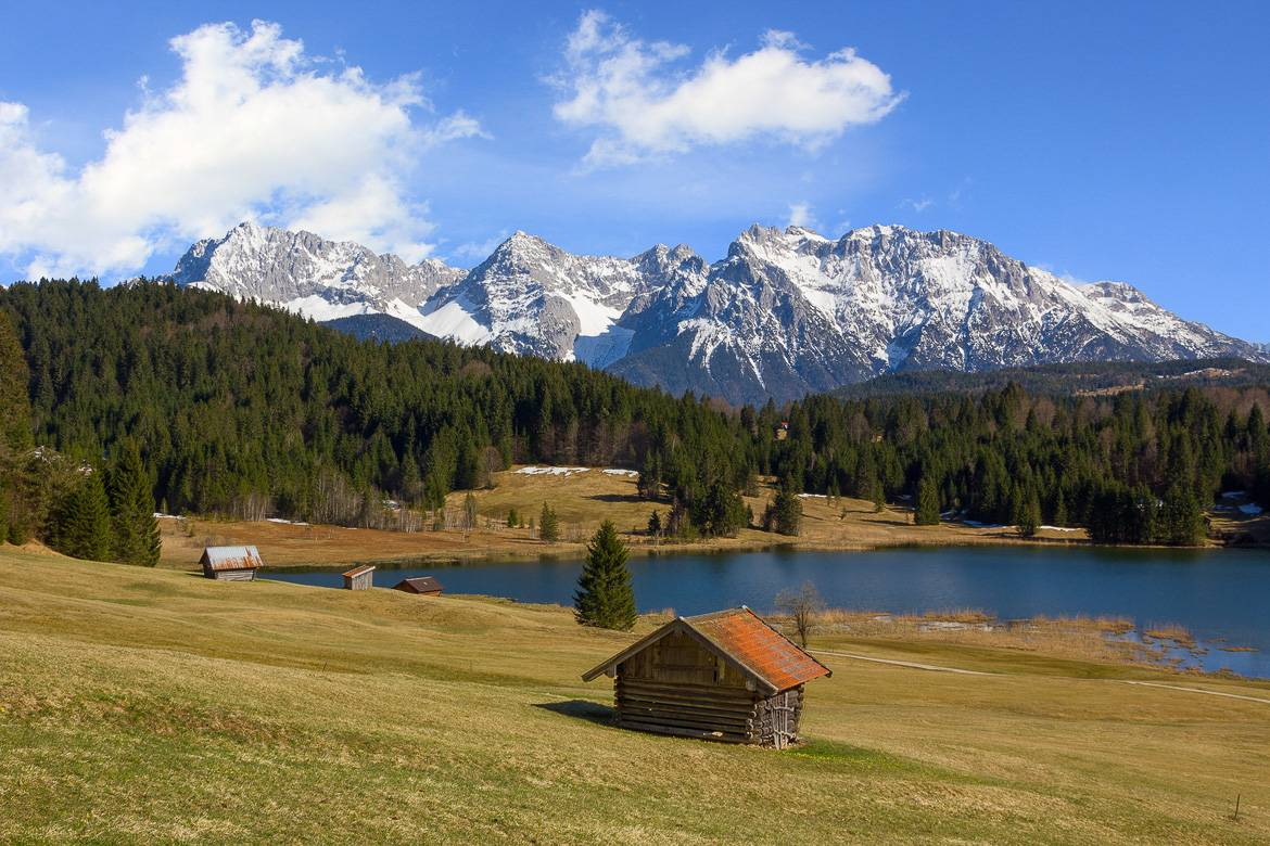 Image of a cabin in front of an alpine mountain range