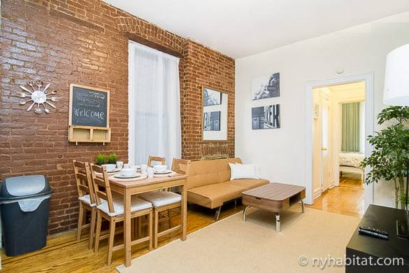 Image of living room with exposed brick, furnished with a futon and dining table in NY-16309