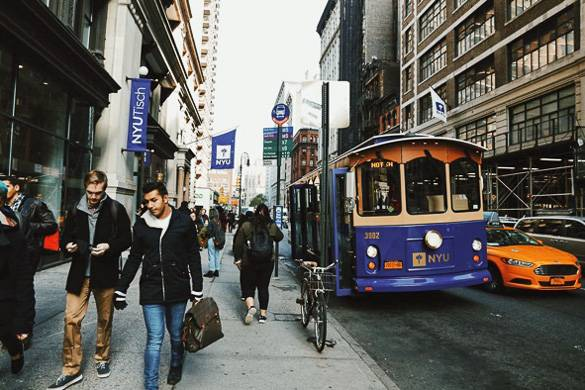 Image of NYU Tisch and a city street with students and an NYU bus