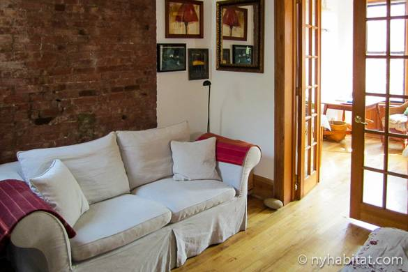 Image of living room of NY-3201 with sofa, French doors and brick walls