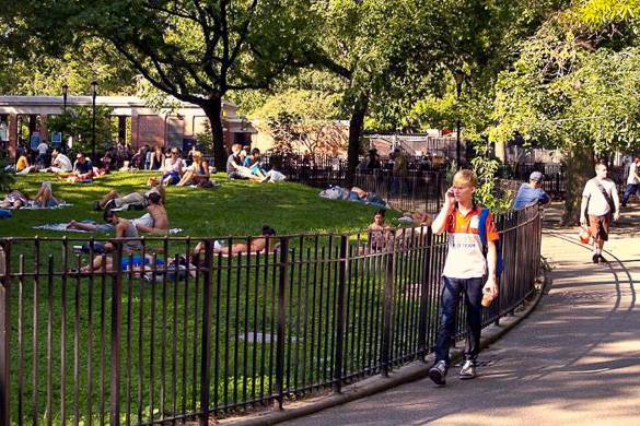 Image of sunbathers and pedestrians in Tompkins Square Park