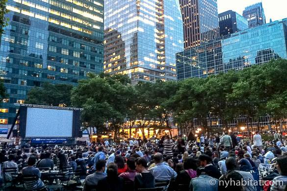 Picture of a crowd watching a movie screen outdoors in Bryant Park