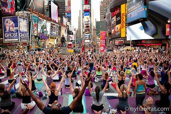 Photo of a crowd doing yoga in Times Square