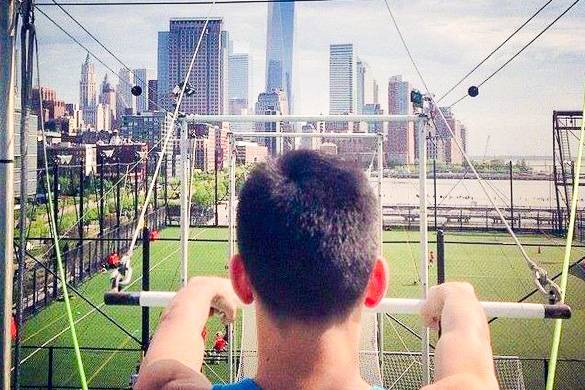 Picture of the back of a man's head as he holds the trapeze and faces the Freedom Tower in the background