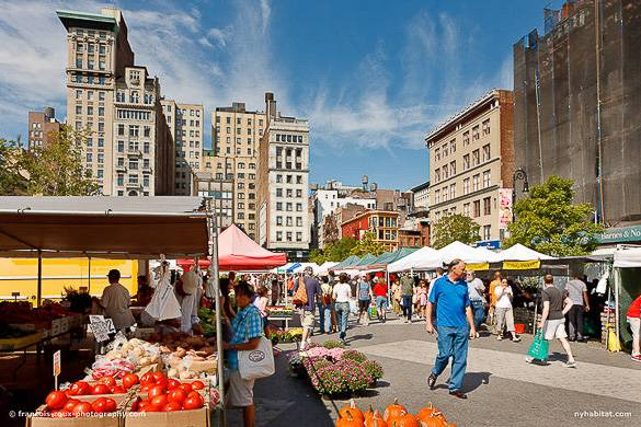 Picture of people walking through a farmer's market in Union Square with tents and NYC skyline in the back