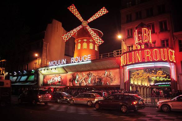 Night shot of the Moulin Rouge with red lights and windmill on top
