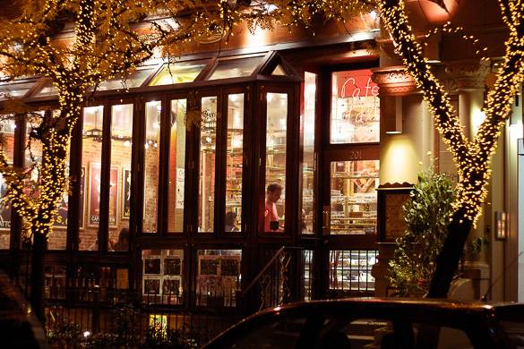 Image of the outside of Cafe Lalo with trees covered in string lights