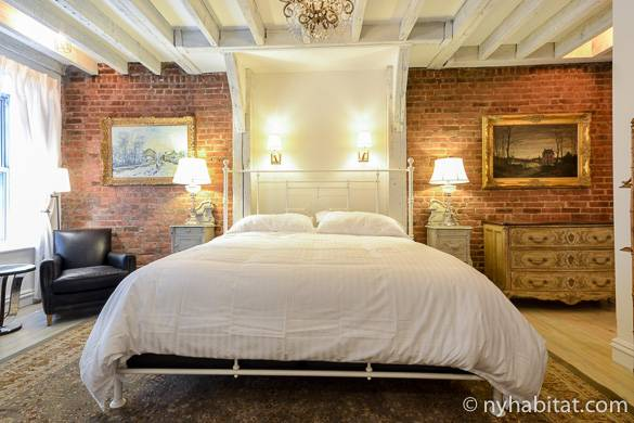Image of bed with chandelier above and exposed brick walls