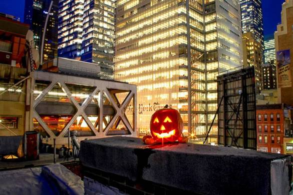 Image of a jack-o-lantern on a city rooftop