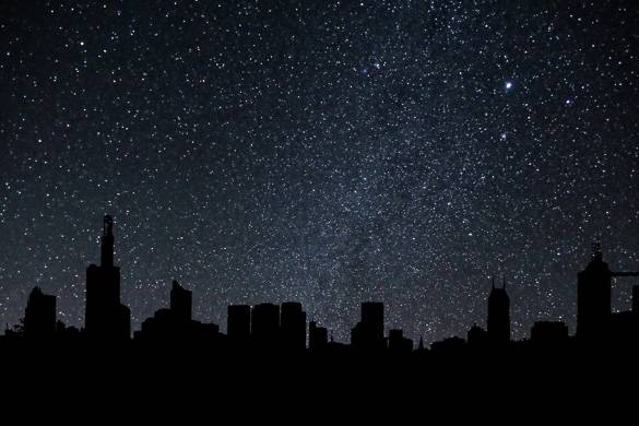 Image of city skyline at night with star-filled sky