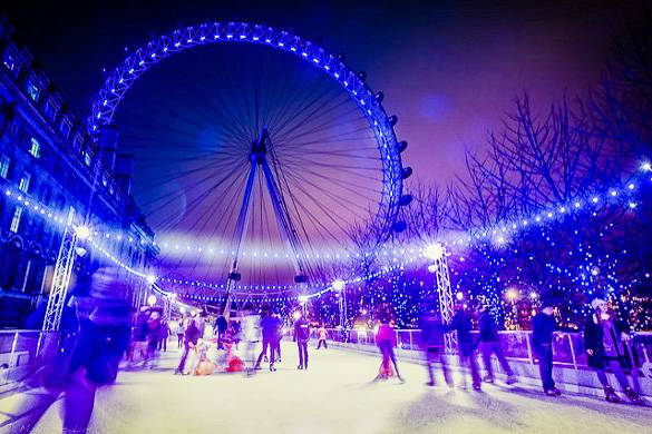Image of people ice skating at night with the illuminated London Eye in the background
