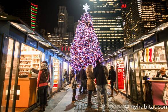 Image of shops and Christmas Tree at the Winter Village at Bryant Park