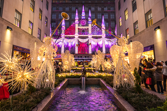 Image of Rockefeller Center with lit up angels with trumpets lining a fountain and Saks holiday lights in the background