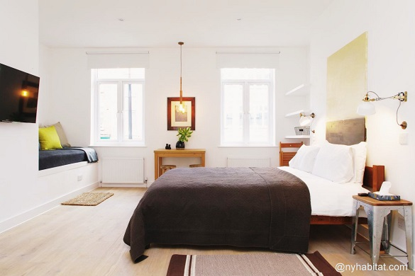 Image of bed with window and seating area in studio LN-1560