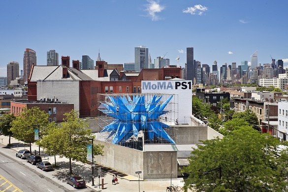 Image of MoMa PS1 in Queens with a giant blue sculpture on the roof and Manhattan skyline in the background