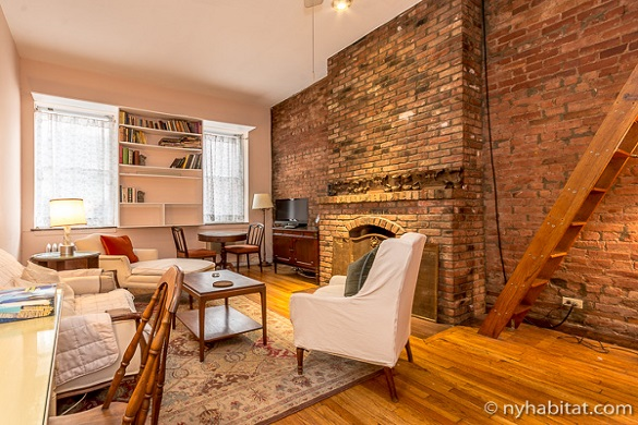 Image of living room area of NY-12100 in a Chelsea brownstone with exposed brick walls and fireplace