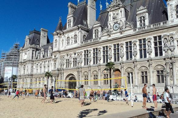Image of people playing beach volleyball in the sand in front of the Hôtel de Ville