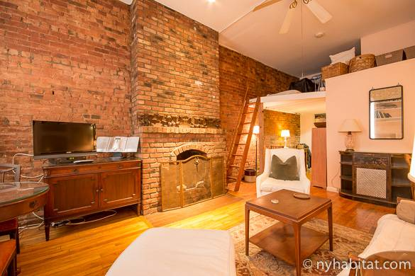 Image of exposed brick wall, fireplace and sleeping loft of NY-12100 in Chelsea
