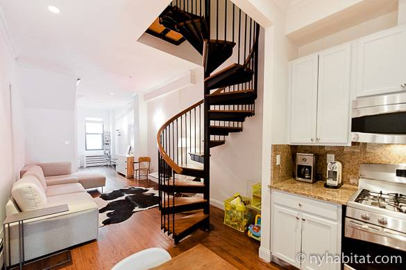 Image of spiral staircase between living room and kitchen in NY-17189, a triplex in Harlem